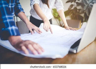Business objects on background of engineers discussing blueprint pointing errors