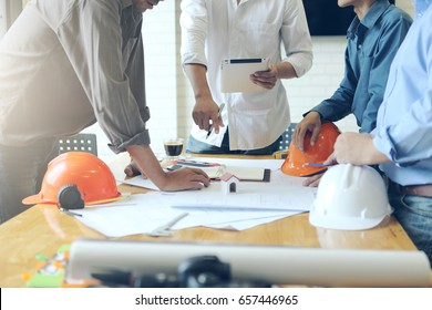 Business objects of team engineers office with construction engineer architect and worker looking building model
