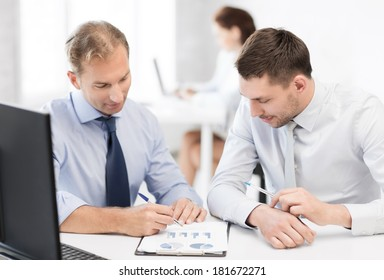 business and office concept - businessmen with notebook discussing graphs on meeting