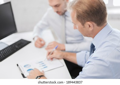 business and office concept - businessmen with notebook on meeting