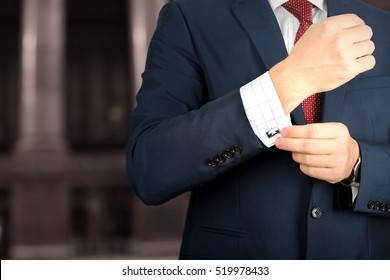 business and office concept -  elegant young fashion  business man in  a blue/navy suit touching at his cufflinks