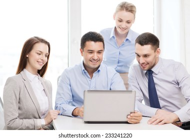 business and office concept - smiling business team working with laptop computer in office
