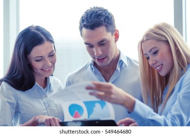 business and office concept - smiling business team looking at clipboard