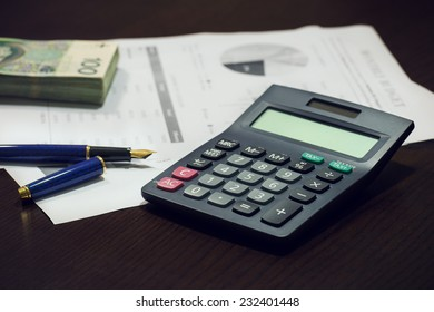 Business office desk with pen calculator charts and money