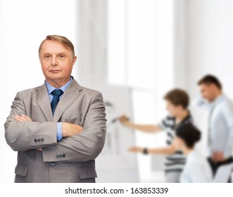 business, office and education concept - serious buisnessman or teacher in suit with team on the back