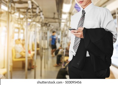 Business office employee using smartphone in subway or sky train, going to work in sunrise morning