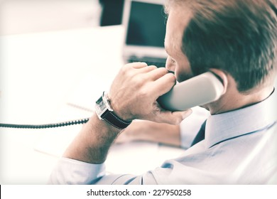 business, office, school and education concept - businessman talking on the phone