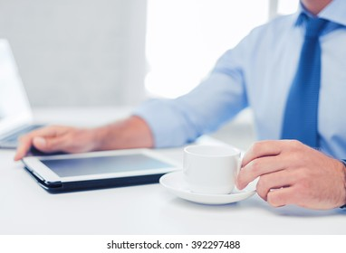 business, office, school and education concept - businessman with tablet pc drinking coffee in office