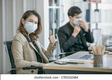 Business office showing thumb up sign on office working together at new normal social distance with table shield partition reduce infection of coronavirus covid-19 pandemic.