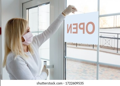 Business office or store shop is open business of novel Coronavirus COVID-19 pandemic. Unidentified person wearing mask hanging open sign in background on front door.