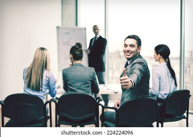 business, office and success concept - confident businessman with team in office showing thumbs up