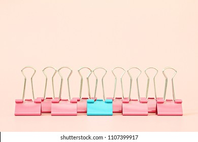 Business, office supplies, leadership, unique, individuality or think different concept : Blue binder clip standing out of pink binder clips on pink background with copy space
