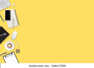 business office table with workspace, laptop computer, coffee cup, notebook, pencil, smartphone and tablet on yellow background