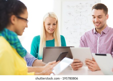 business, office, technology and startup concept - smiling creative team with table pc and laptop computers working in office