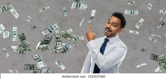 business, office worker and people concept - smiling indian businessman pointing finger at money rain over grey background