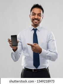 business, office worker and people concept - smiling indian businessman pointing finger to blank screen of smartphone over grey background