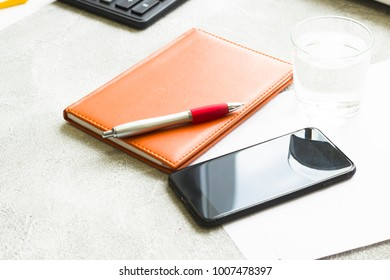 Business Office Workplace Concept with a planner in an orange leather cover, a black smartphone and a pen, grey concrete background