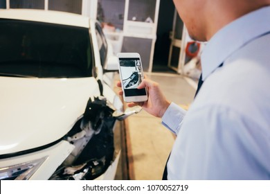 Business officer taking a photo of damaged and wrecked car bender in garage as evidence for insurance and verification purpose