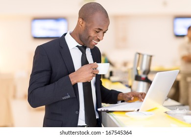 Business on the go. Cheerful young African man in formalwear using his laptop while standing at the bar