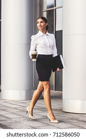 Business on the move. Beautiful and young business woman looking away and keeping cup of coffee in one hand and folder with documents in another while walking outdoors.