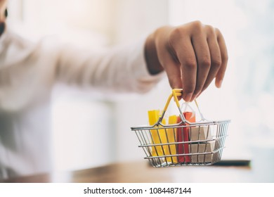 Business online shopping and delivery concept. Woman hand carry shopping basket with shopping bag and box inside.