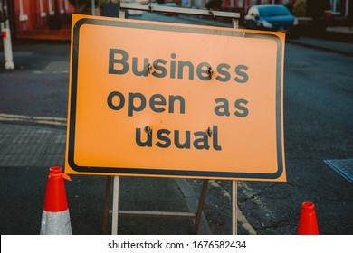 Business open as usual. Yellow sign stating business open as usual during lockdown and road works. Business open as usual sign on road. Business open as usual sign during coronavirus covid-19 pandemic