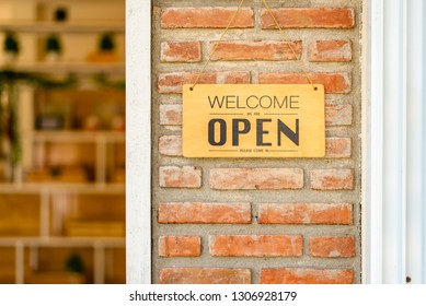 Business open and welcome wooden sign board at bricks wall beside the door.