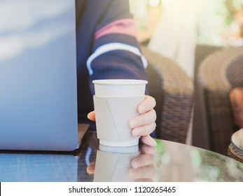business with outdoor travel concept from beauty woman hand use laptop and put paper cup of coffee at counter of coffee bar