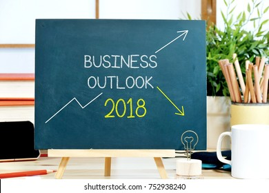 business outlook 2018 with the trend chart both up trend and down trend wrote on the chalkboard with the background of workspace in the office
