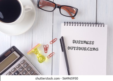 BUSINESS OUTSOURCING text on notebook.coffee,calculator,pen,rubber stamp,glasses on the desk.top view.