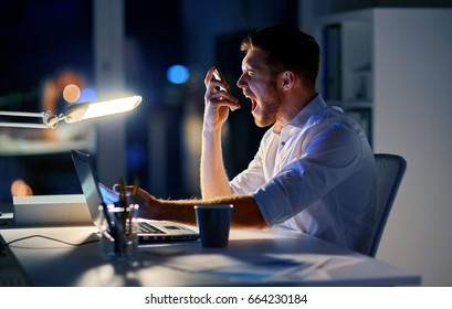 business, overwork, people, deadline and technology concept - angry businessman with laptop computer calling on smartphone at night office and screaming