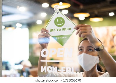 Business owner Asian woman wear protective face mask ppe hanging open sign at her restaurant / café, open again after lock down due to outbreak of coronavirus covid-19 - Shutterstock ID 1723056670