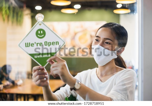 Business owner Asian woman wear protective face mask ppe hanging open sign at her restaurant / café, open again after lock down due to outbreak of coronavirus covid-19