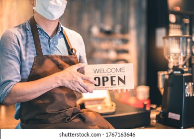 Business owner attractive young Asian man in apron hanging we're open sign on front door  welcoming clients to new cafe. Happy waiter with protective face mask holding open sign while stand at cafe .