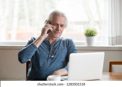 Business owner confident old man sitting at table look at pc screen talking on phone solve important issues distantly. Client make call by hotline to consultant, elderly medicine health care concept