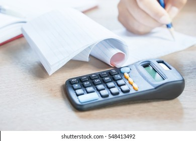 business owner doing their monthly accounting with the calculator in the foreground
