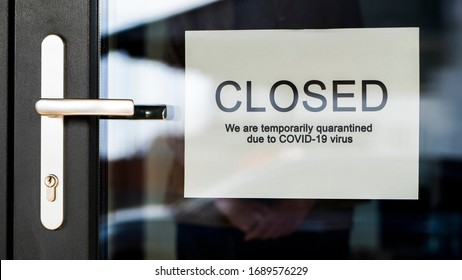 Business owner hangs on door announcement of closure due to coronavirus quarantine.