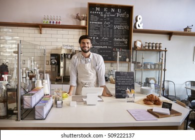 Business owner standing behind the counter at a coffee shop