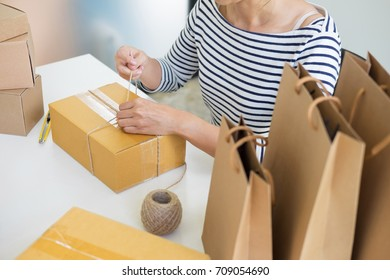 Business owner woman working online shopping prepare product packaging process at her home, young entrepreneur concept