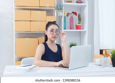 business owner working at home office packaging on background. online shopping SME entrepreneur working Young Women happy after new order from customer.