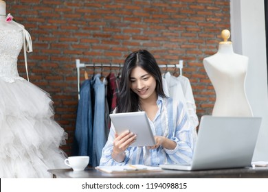 business owner,Fashion designer drawing new sketches collection and sent a business e-mail to client.satisfied with sales success,working using laptop ,digital tablets in Designers Stylish in workshop