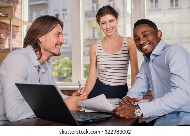 Business partner having meeting in office and discussing something. Mixed race business team using laptop and discussing project.