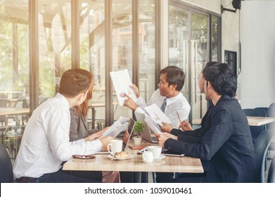 business partner marketing team discussing market research and brainstorming with colleagues in a meeting. Multiethnic businesspeople having a meeting in conference room looking at document