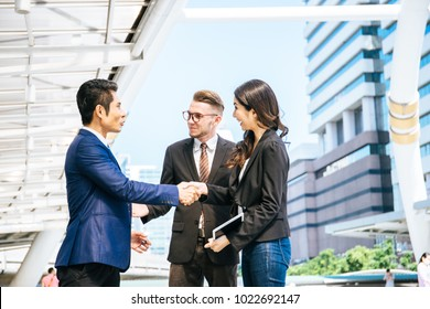 Business partner shaking hands and smiling while meeting in front of office. Business and success concept.