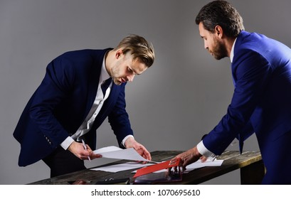 Business partner signs the document under pressure. Unfavorable deal concept. Men in suit or businessmen with tense expression on dark background. Businessman requires signing a contract.