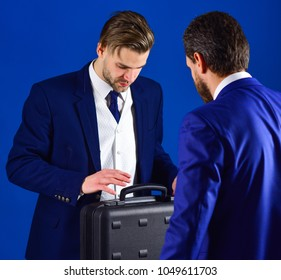 Business partners with busy face on blue background. Businessmen speaking about transaction. Business handover concept. Men in suit or businessmen meet for handover of black briefcase.
