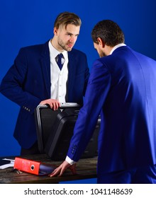 Business partners with calm face on blue background. Men in suit or businessmen meet for handover of black briefcase and red folder. Businessmen speaking about transaction. Business handover concept.