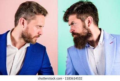 Business partners competitors or office colleagues in suits with tense bearded faces close up. Hostile or argumentative situation between opposing colleagues. Business competition and confrontation.