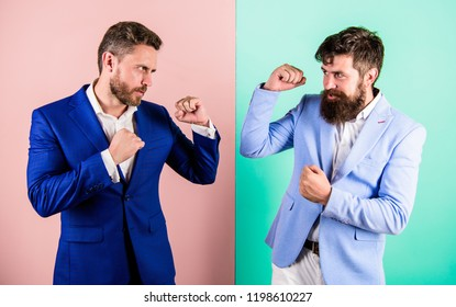 Business partners competitors or office colleagues in suits with tense faces ready to fight. Hostile or argumentative situation between opposing colleagues. Business competition and confrontation.