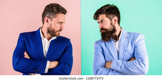 Business partners competitors in suits with tense bearded faces. Businessmen stylish appearance jacket pink blue background. Tense face expression competitors. Business competition and confrontation.